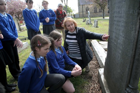 ETCHED IN HISTORY: Classmates look on as Lily Beal and Megan Jones, from Ings Farm School, in Redcar, are shown details of a war grave in Redcar Cemetery by local historian Janet Philo