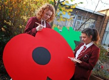 SEEING RED: Sarah Sharp, 13, and Chloe Toward, 13, paint a giant poppy. Picture: SARAH CALDECOTT