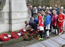 YOUNG AND OLD: Players from South Park Rangers place crosses on the war memorial at Smith's Dock Park, Normanby. Picture: TOM BANKS
