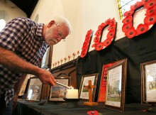FLAME TRIBUTE: Church volunteer Ian Wood lights a candle at the exhibition at St John's Church in Darlington. Picture: ANDY LAMB