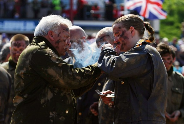 British and German troops share a cigarette as the meet in No Man's Land during the truce re-enactment