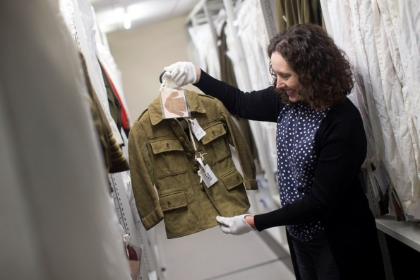 A curator examines an army jacket in the DLI Collection at Sevenhills