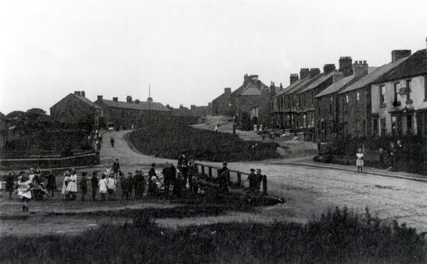 LOOKING BACK: Kirk Merrington in about 1920. Chapel Street is the rough road that rises up to the right of the main road, with Edward and Mary's home at the highest point. The children in the foreground are playing in what remains of a pond which was once in the centre of the road - now Ramshaw and Coronation terraces occupy this spot. Picture courtesy of Ann and Dennis Arthur