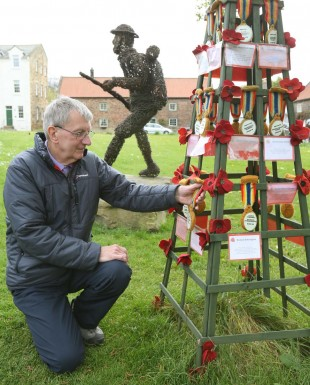 Historian Ian Pearce hanging one of the knitted medals near the wicker sculpture of the WWI soldier at Great Ayton. Picture: Richard Doughty Photography.