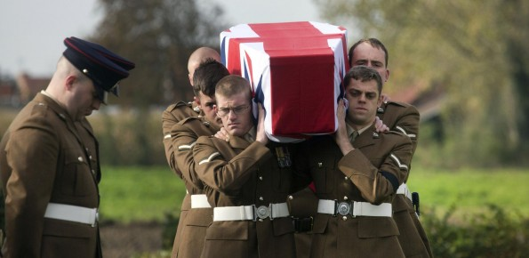 PAYING TRIBUTE: Two British soldiers bow their heads as a detail carry the casket of a World War One soldier during a re-burial ceremony in Bois-Grenier, France.