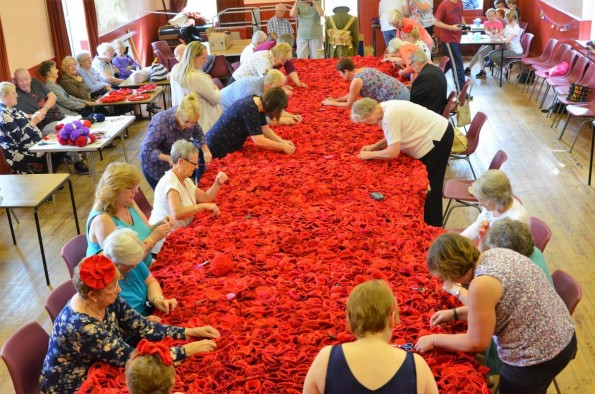EFFORT: Poppies are attached to nets by dozens of volunteers ahead of an unveiling in October