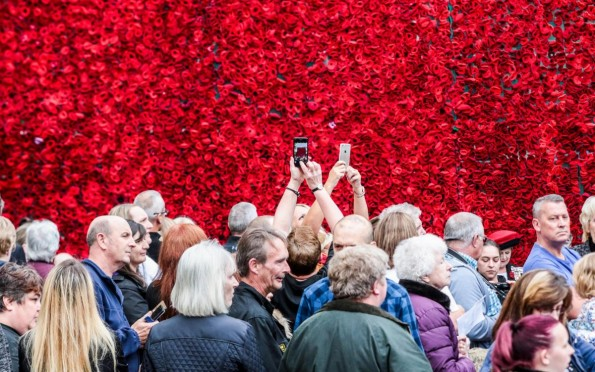 EXCITEMENT: A large crowd gathered to see the grand unveiling of thousands of poppies suspended in from of the Church Hall in West Cornforth