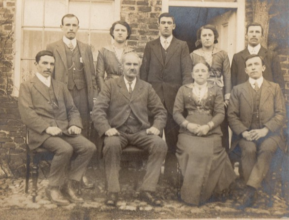 PHOTO: A  photo of Henry Johnson with his family taken before he left for the war. Henry (front row, far left) and his brother James (front row, far right) are sat on either side of their parents.