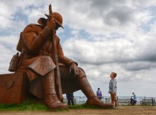 "A young boy looks up at the imposing giant sculpture of ""Tommy"", the World War One soldier, which is set to remain on Seaham's seafront after a small community of residents raised £85,000 to keep the nine-foot sculpture"